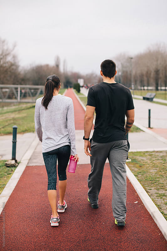 Couple walking on a jogging track  by Marija Mandic for Stocksy United