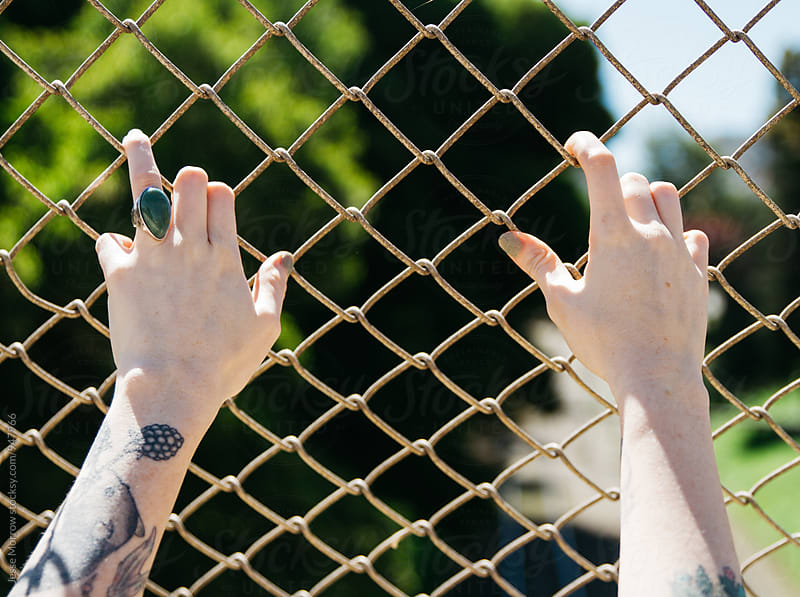young woman with tattoos hands on chain link fence  by Jesse Morrow for Stocksy United