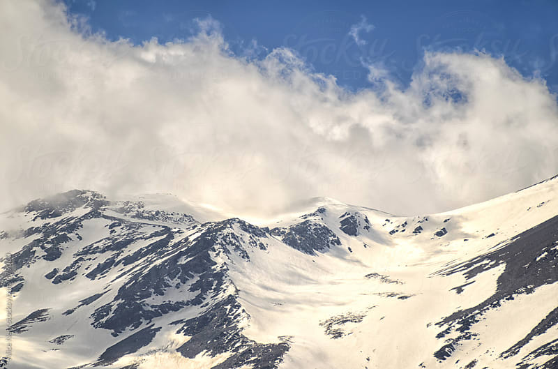 Clouds raising from snowy mountain summit by Alice Nerr for Stocksy United