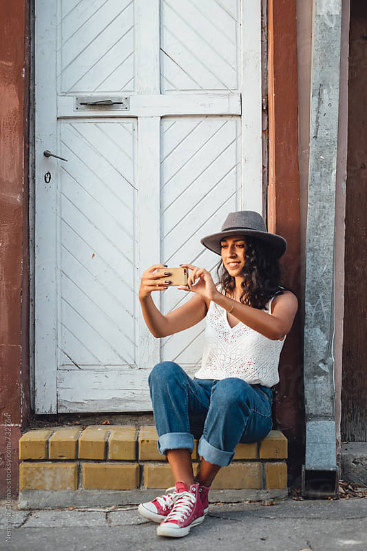 Curly Bolivian Teen Using Her Smartphone to Take Selfie by Nemanja Glumac for Stocksy United