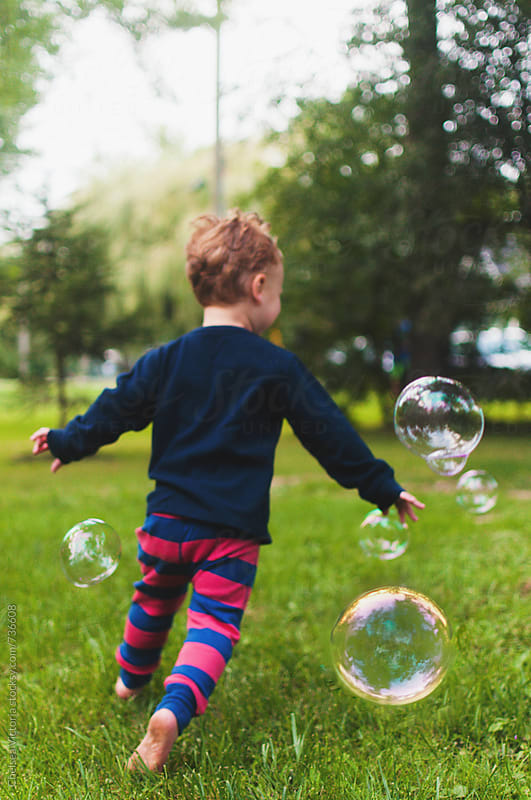 A child plays with bubbles by Chelsea Victoria for Stocksy United