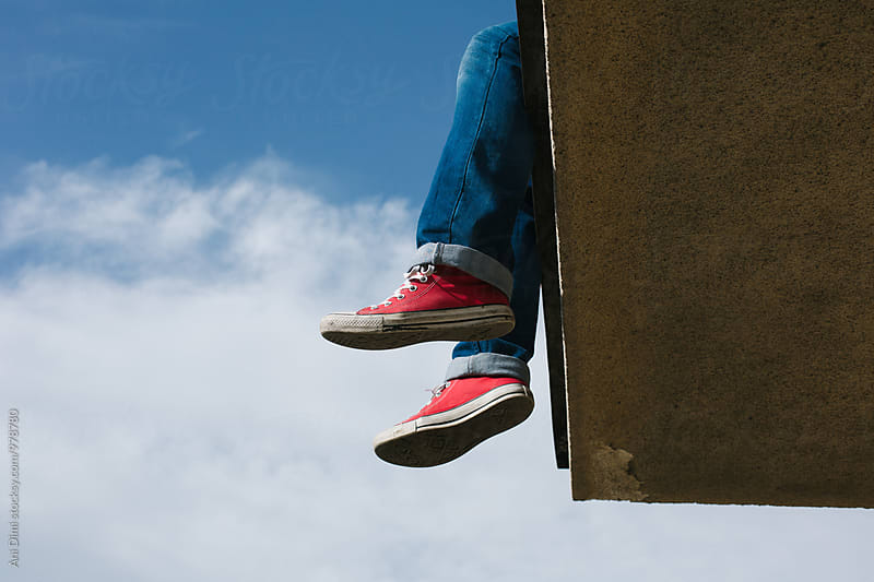 Legs with sneakers  hanging off a rooftop by Ani Dimi for Stocksy United