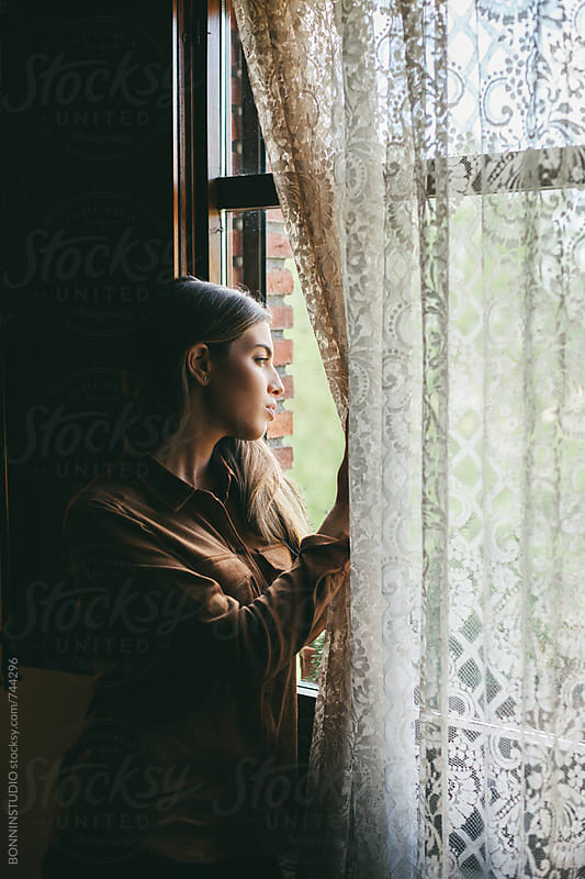 Woman looking through the window standing in a rural home. by BONNINSTUDIO for Stocksy United
