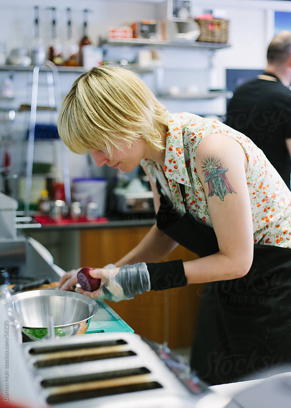 Female cook preparing fresh produce in a busy cafe. by Darren Muir for Stocksy United
