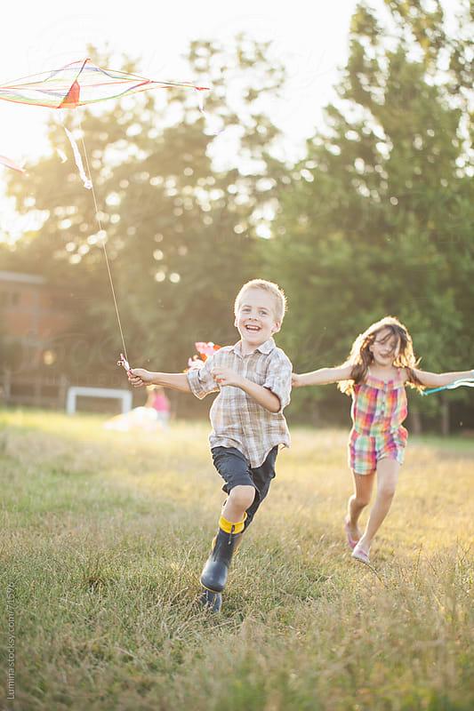Smiling Children Flying a Kite by Lumina for Stocksy United
