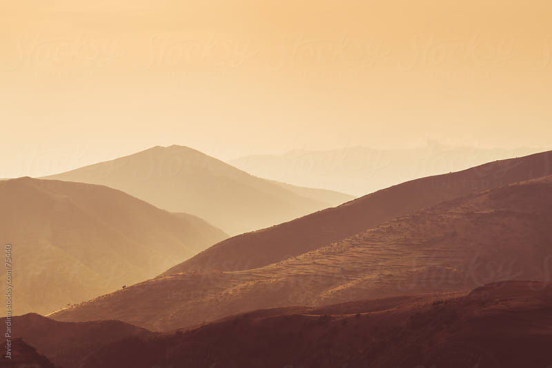 silhouettes of mountains with red light by Javier Pardina for Stocksy United