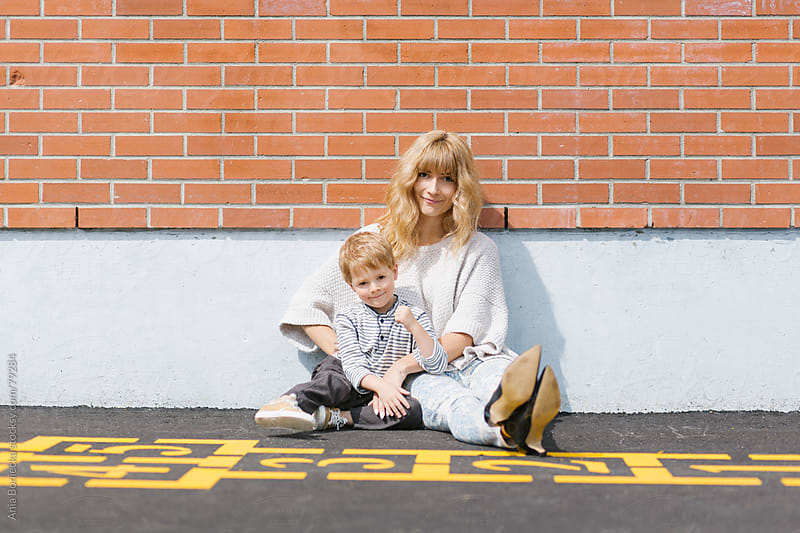 Mother and son sitting by a brick wall in a school playground by Ania Boniecka for Stocksy United