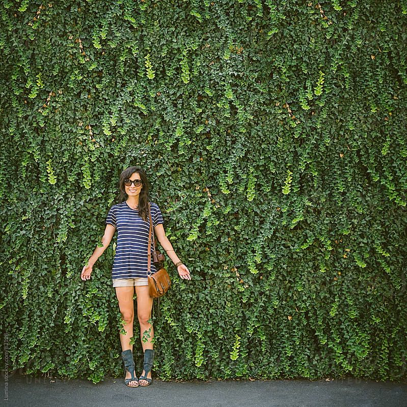 Smiling Woman Standing by a Wall Covered in Leaves by Lumina for Stocksy United