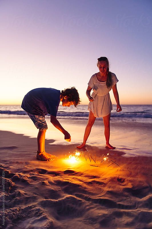 Brother and sister with sparklers at the beach at night by Angela Lumsden for Stocksy United