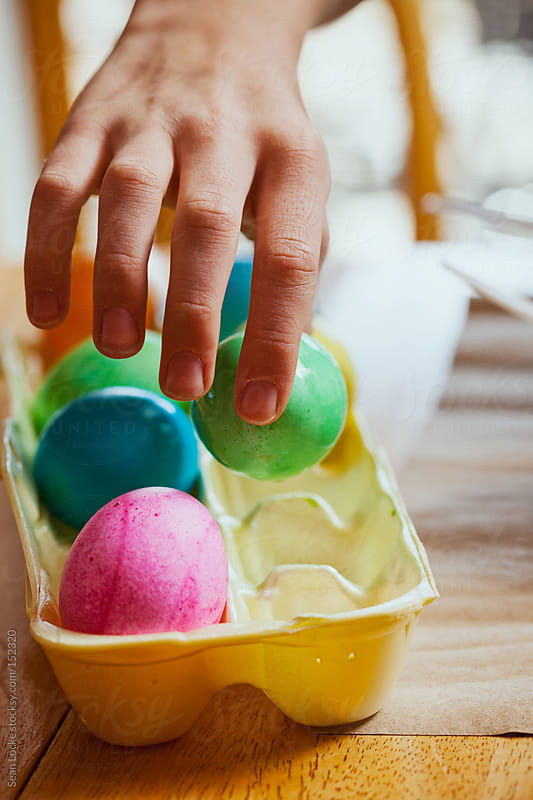 Easter: Placing Green Colored Egg Into Carton To Dry by Sean Locke for Stocksy United