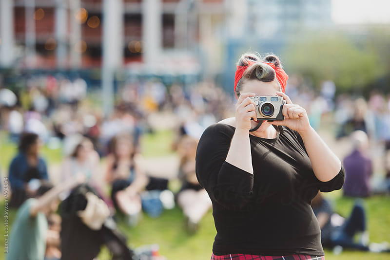 Woman taking a picture with film camera by Lauren Naefe for Stocksy United