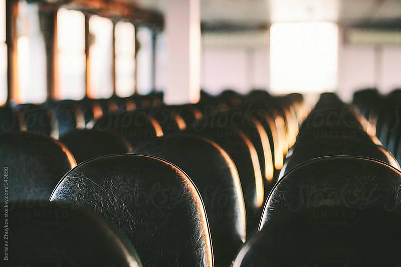 Empty seats on ferry light by sunset by Borislav Zhuykov for Stocksy United