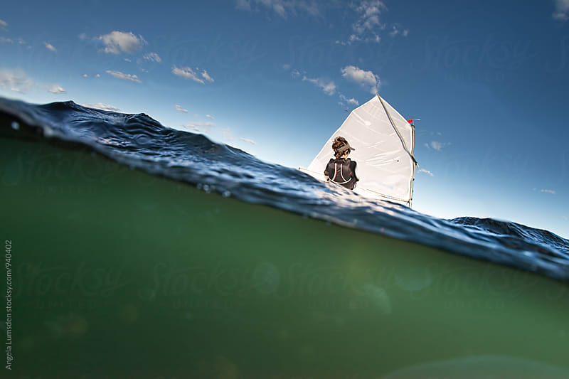 Over under split image of a boy sailing an optimist dinghy  by Angela Lumsden for Stocksy United
