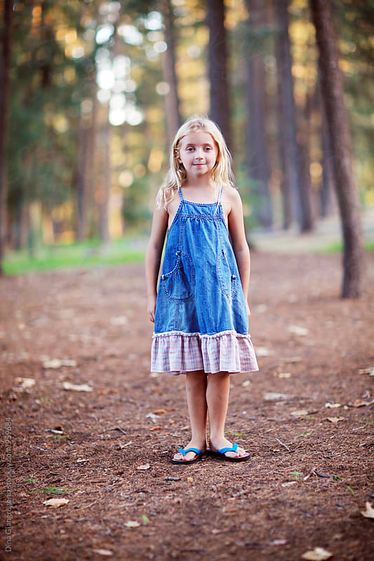 Little Blonde Girl WEaring Denim Dress Standing In The Woods by Dina Giangregorio for Stocksy United