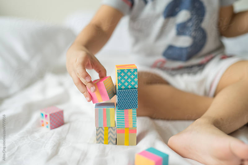 Kid playing with colourful building blocks by Alita Ong for Stocksy United