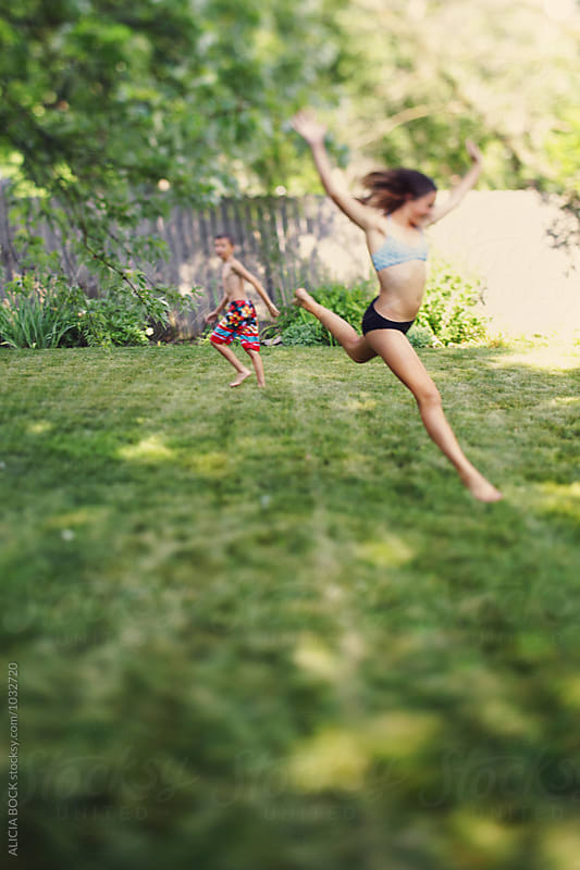A Teenage Girl Leaping Through A Sprinkler On A Hot Summer Afternoon by ALICIA BOCK for Stocksy United