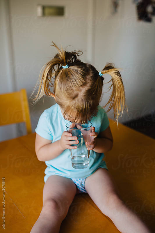 Cute toddler girl with pigtails looking down into a glass of water while sitting on the kitchen table. by Jessica Byrum for Stocksy United