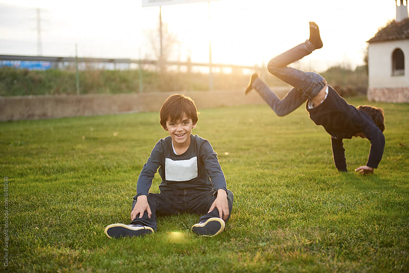 Smiling boy sitting against of other boy rolling on grass by Guille Faingold for Stocksy United
