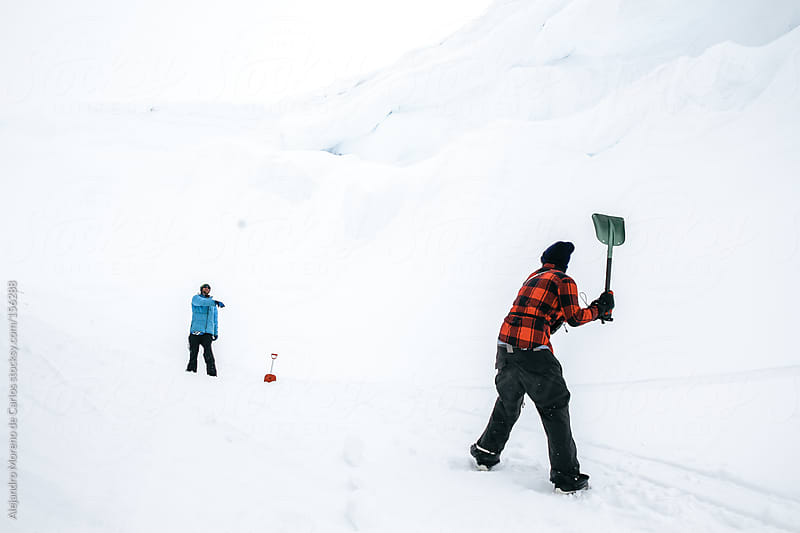 Friends playing baseball on snow with a shovel by Alejandro Moreno de Carlos for Stocksy United
