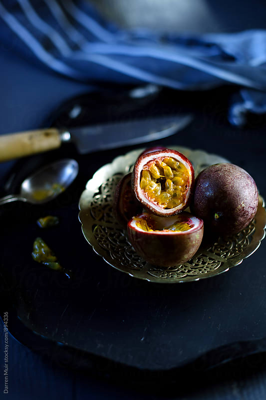 Passion fruit halves in a metal bowl. by Darren Muir for Stocksy United
