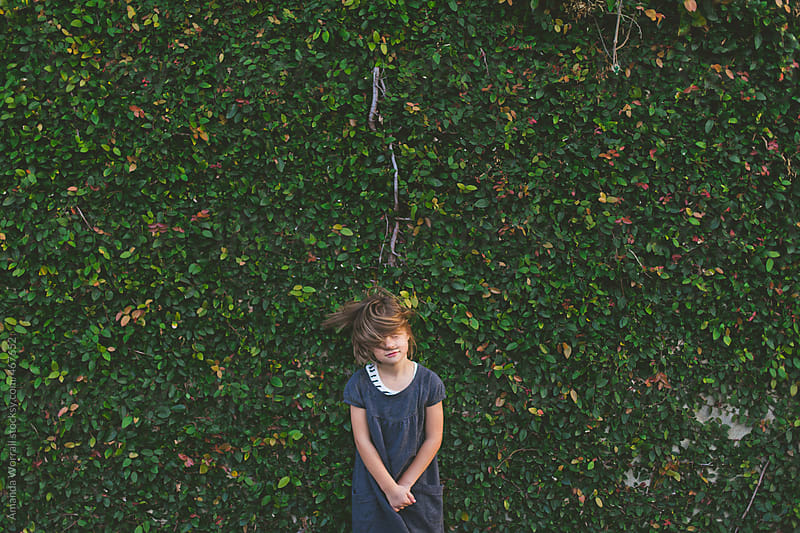 Young girl flips hair while standing in front of a vine-covered wall by Amanda Worrall for Stocksy United