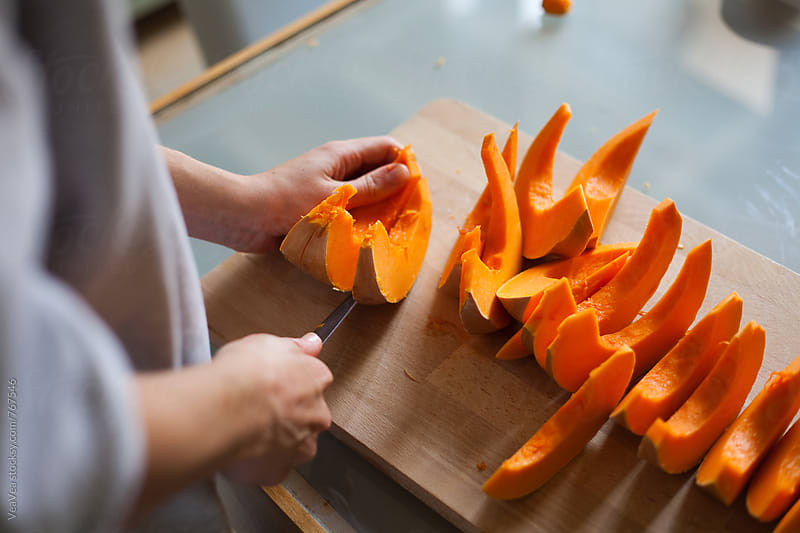 Female hands cutting slices of pumpkin  by VeaVea for Stocksy United