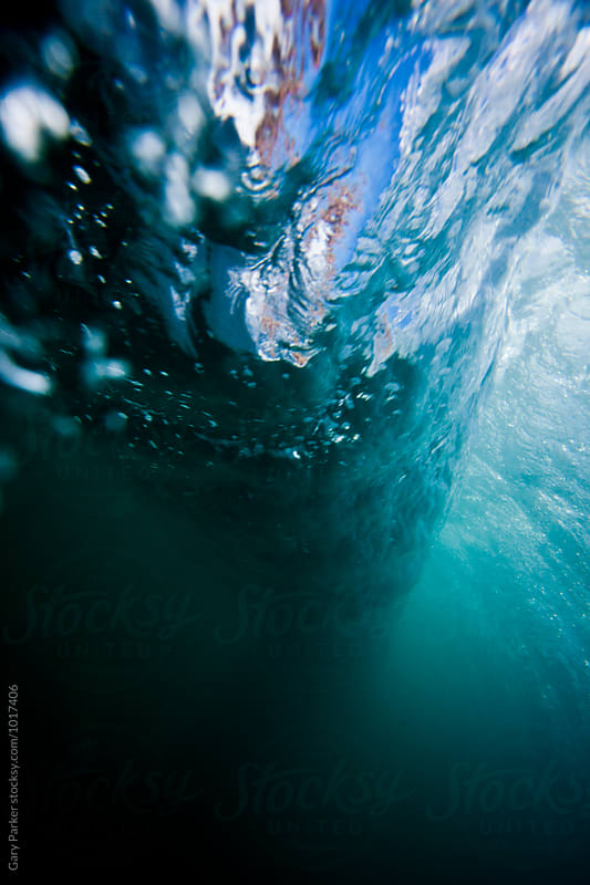 A wave breaking underwater by Gary Parker for Stocksy United