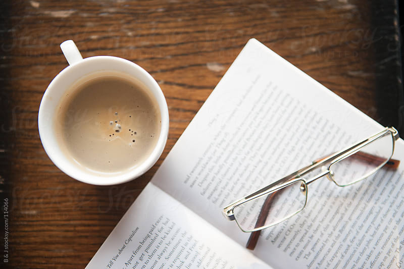 reading a book and heaving a cup of coffee by B & J for Stocksy United