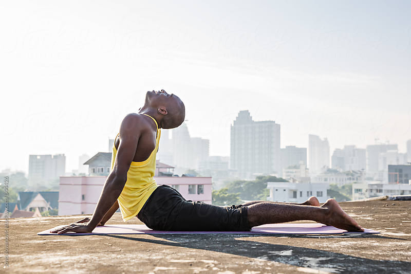 Muscular and healthy young man in a cobra yoga position on a city skyscraper rooftop  by Jovo Jovanovic for Stocksy United