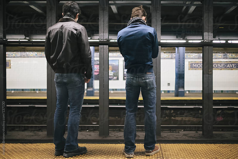 Young Men Friends in Tight Jeans and Bomber Jackets Waiting for Train in New York Subway Station by Joselito Briones for Stocksy United