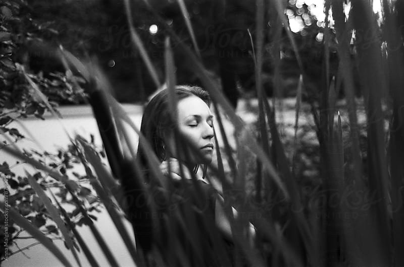 A black and white portrait of a young woman hiding in the grass by Anna Malgina for Stocksy United