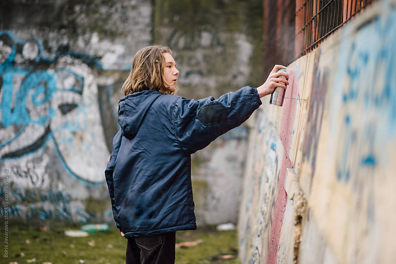 Boy drawing a graffiti on the wall by Boris Jovanovic for Stocksy United