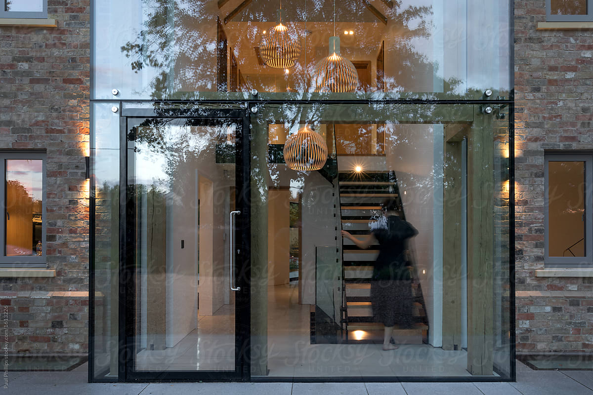 View modern house lights Exterior Evening View Of The Glass Entrance To Modern House With Lights On And Woman The Wow Style Evening View Of The Glass Entrance To Modern House With Lights On