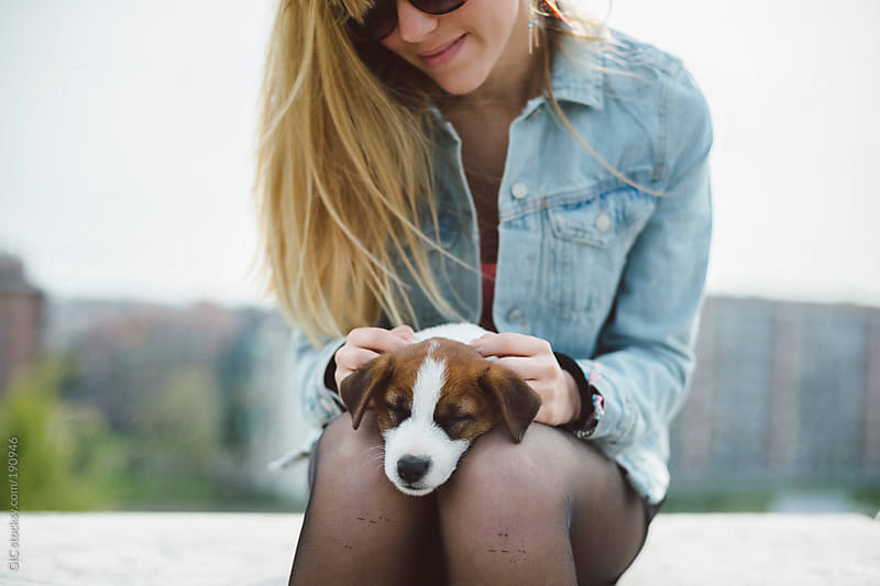 Young woman embracing her puppy in the city by GIC for Stocksy United