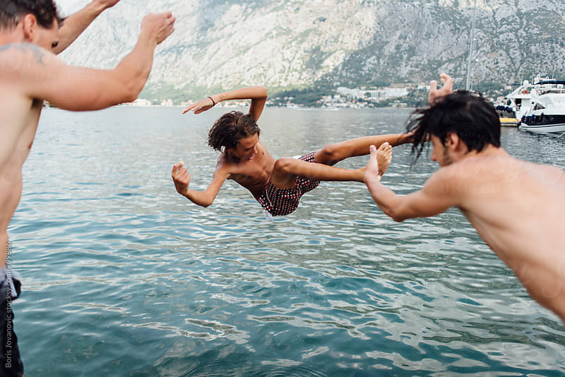 Friends throwing a young boy in to the water by Boris Jovanovic for Stocksy United