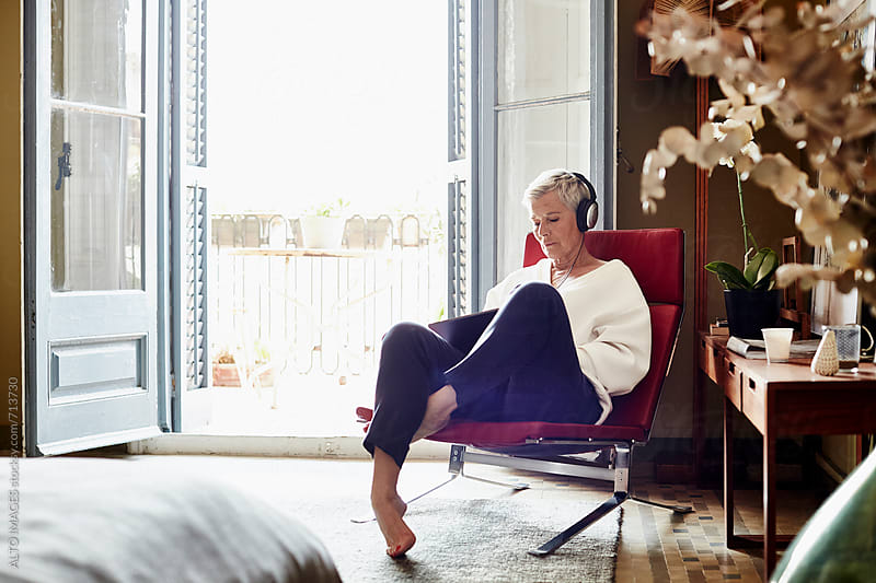 Senior Woman Listening Music While Sitting On Chair At Home by ALTO IMAGES for Stocksy United