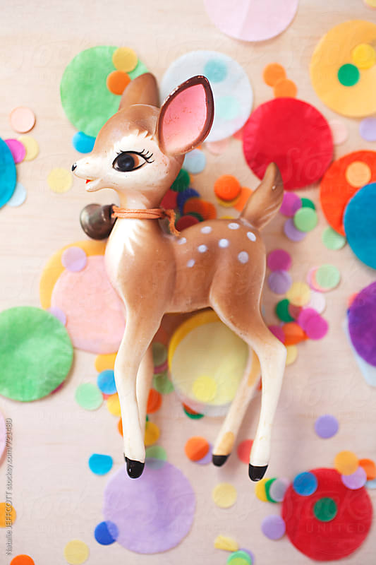 bright and colourful confetti with vintage Christmas deer ornament by Natalie JEFFCOTT for Stocksy United