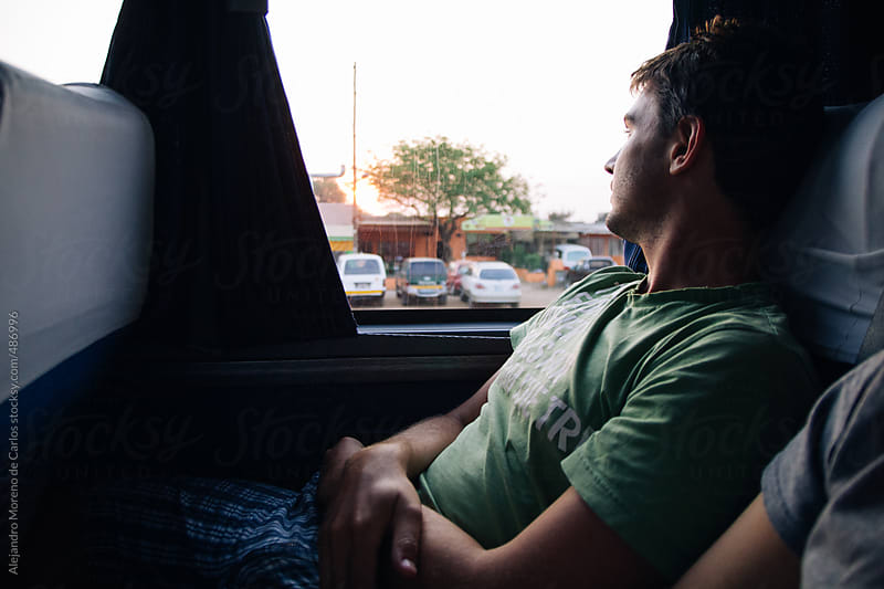 Young man traveling on a bus at sunset during adventure travel by Alejandro Moreno de Carlos for Stocksy United