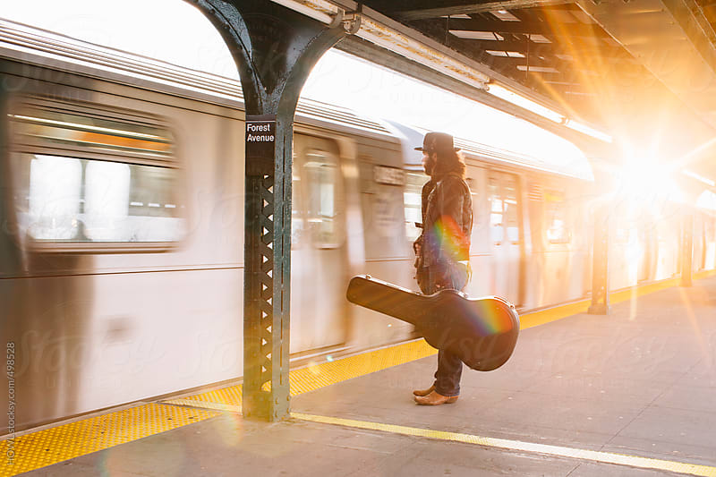 A musician waits patiently for the NYC Subway  by HOWL for Stocksy United