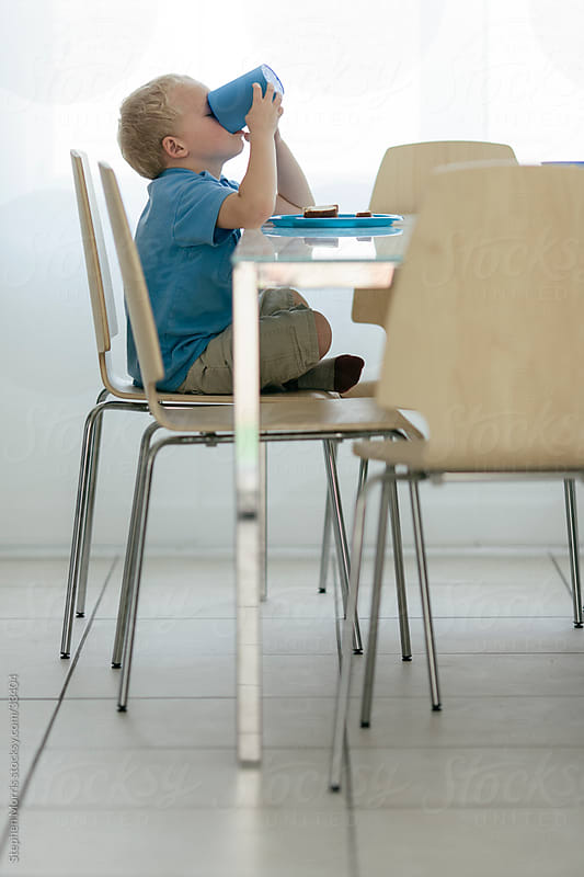 Boy Eating lunch in Modern Dining Room by Stephen Morris for Stocksy United