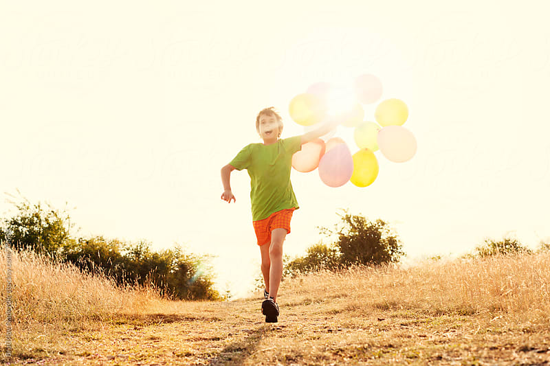 Young boy running down the hill with balloons in his hand by Bratislav Nadezdic for Stocksy United