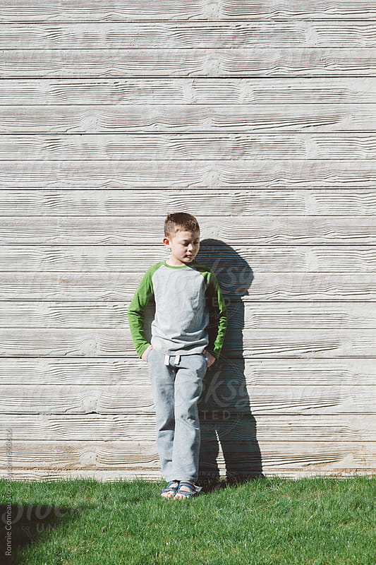 Boy Standing Against Concrete Wall by Ronnie Comeau for Stocksy United