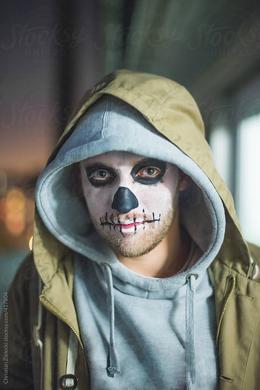 portrait of a man with skull halloween make up  by Christian Zielecki for Stocksy United