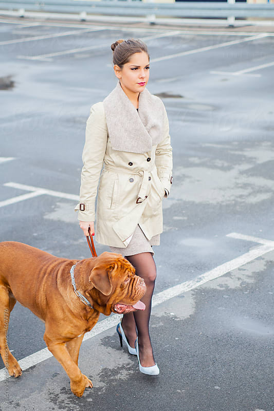 Young woman having a walk on street with her dog. by Audrey Shtecinjo for Stocksy United