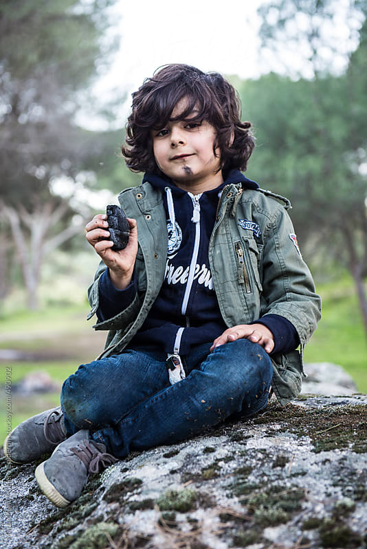 Child with face smeared with charcoal sitting on a stone in the forest by Marta Muñoz-Calero Calderon for Stocksy United