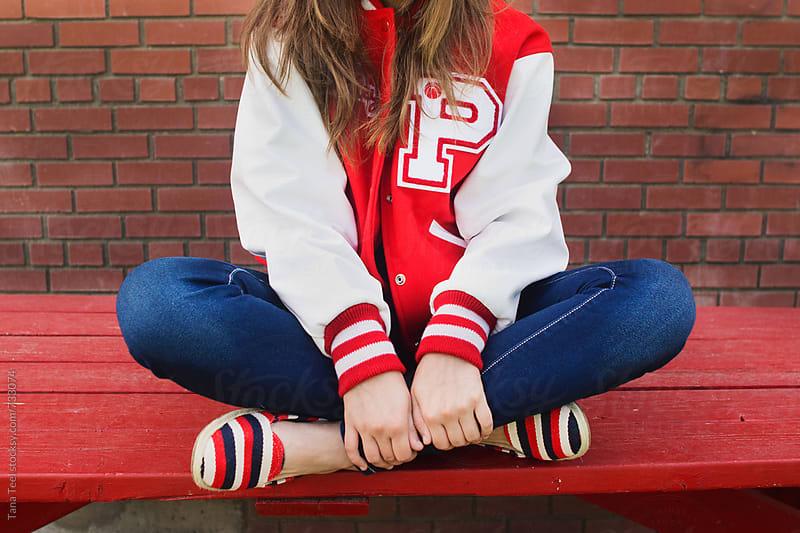 Teenage girl wearing letterman jacket sits crossed leg on table by Tana Teel for Stocksy United