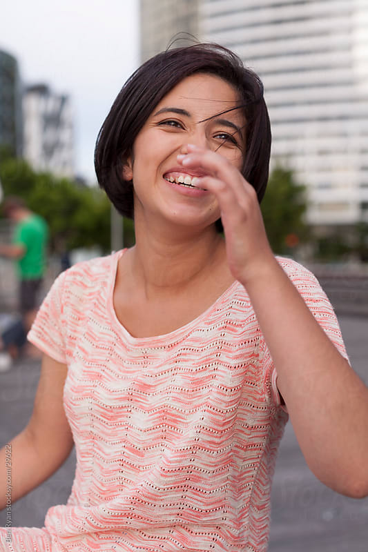 Hispanic woman laughing heartily by Ben Ryan for Stocksy United