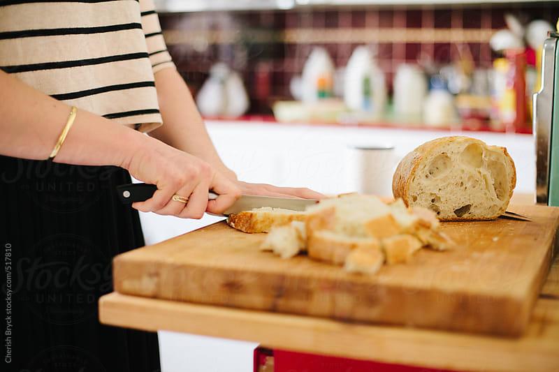 Cute woman cuts bread. by Cherish Bryck for Stocksy United