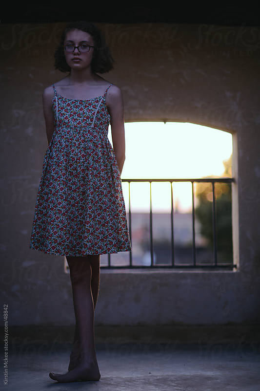 Caucasian girl standing on a balcony at sunset by Kirstin Mckee for Stocksy United