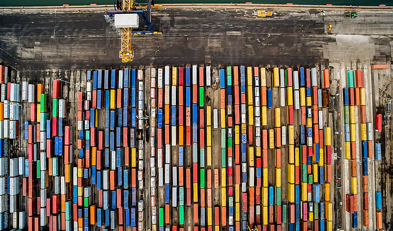 An overhead aerial view of a shipping dock quayside full of different colored shipping containers by Andy Campbell for Stocksy United